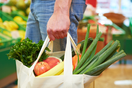 Mann trägt vollen Beutel mit Obst und Gemüse im Supermarkt